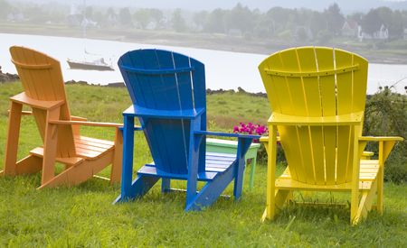Wooden Adirondack chairs positioned with a view of the river.