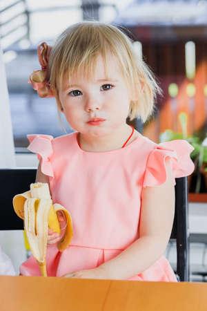Foto für A girl eats a banana - Lizenzfreies Bild