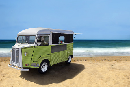 Green retro fast food truck on the beach, vertical template with copy space