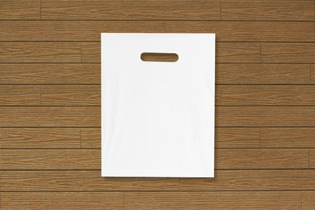 Blank plastic bag mock up on wooden floor. Empty white polyethylene package mockup. Consumer pack ready for logo design or identity presentation. Commercial product food packet handle.