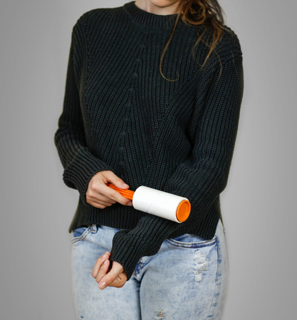 Girl cleans clothes sticky roller. Close up. Isolated.
