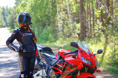 KRASNOYARSK, RUSSIA - June 23, 2018: Beautiful girl motorcyclist in full gear and helmet on a red and black Honda 2005 CBR 600 RR (PC37)