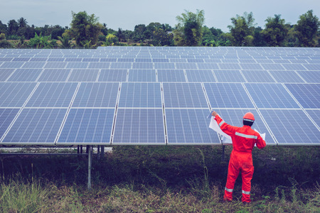 Photo pour engineer in solar power plant working on installing solar panel ; smart operator holding blueprint for installing equipment in solar power plant - image libre de droit