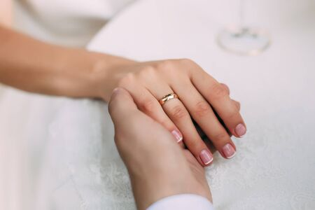 Photo pour Groom holds brides hand with ring on her finger, close-up view - image libre de droit