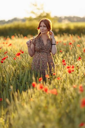 Photo pour Redhead woman on green field with poppies - image libre de droit
