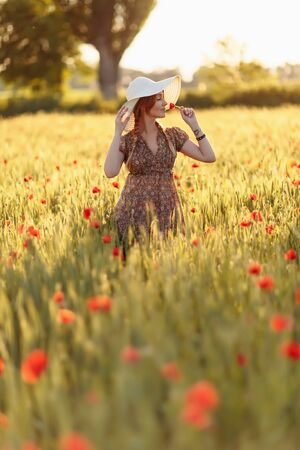 Photo pour Redhead woman in hat on green field with poppies - image libre de droit