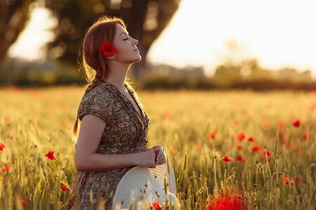 Photo for Redhead woman with hat on green field with poppies - Royalty Free Image