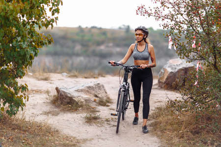 Photo for Fit young woman wearing sportswear standing with her bicycle on rocky background - Royalty Free Image