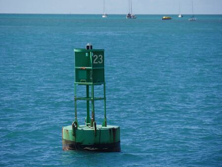 Photo for A bouy floats in the ocean some meters away from the pier - Royalty Free Image