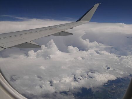 Photo pour Storm clouds seen from an airplane window, with an airplane wing in view. - image libre de droit