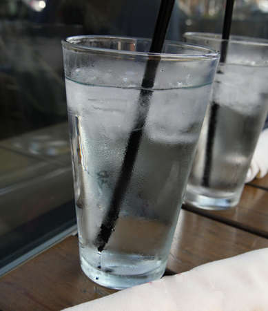 Photo pour Tall glasses of ice-cold water with black straw - image libre de droit
