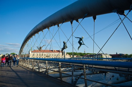 Foto de Krakow,Poland - May 12, 2018: Bridge in Krakow the K adka Ojca Bernatka or Father Bernatek Footbridge across the Vistula river, Krakow, Poland. Most artistic and quirky suspension bridge of Krakow. The acrobatic figures by Polish artist Jerzy Jotki Kedzio - Imagen libre de derechos