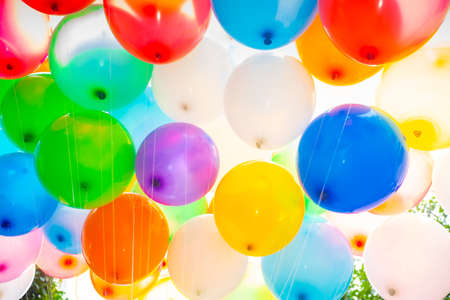 Photo for Sunlight against colorful gas-filled balloons attached to the yarn. Colorful balloons background. - Royalty Free Image