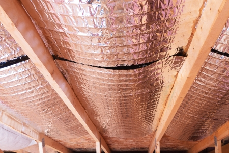 Insulating of attic with fiberglass cold barrier and reflective heat barrier used as baffle between the attic joists to increase the ventilation to reduce humidification