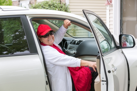 Senior lady with red hat sitting on the passenger seat getting ready close the door and hit the road, she has genuine smile on her face