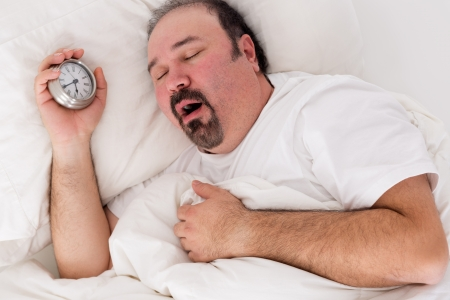 Lethargic tired man lying in bed yawning as he struggles to wake up unmotivated to start the new day and content to rather continue lying in bed as he holds his alarm clock in his hand