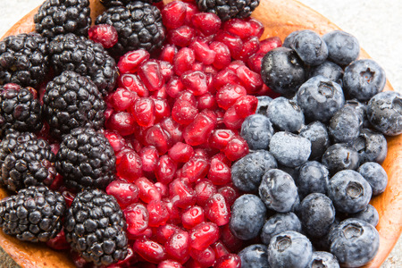 Foto für Closeup of juicy mixed berries and succulent pomegranate seeds in a wooden bowl with blackberries and blueberries for a healthy dessert rich in antioxidants - Lizenzfreies Bild
