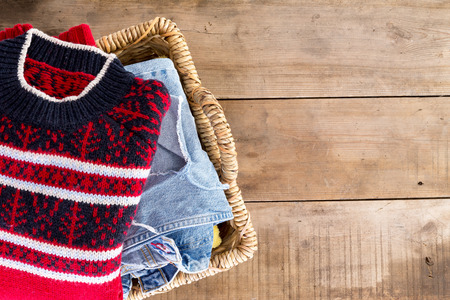 Wicker laundry basket filled with clean fresh washed winter clothes viewed from overhead standing at an angle on rustic wooden boards with copyspace on the right