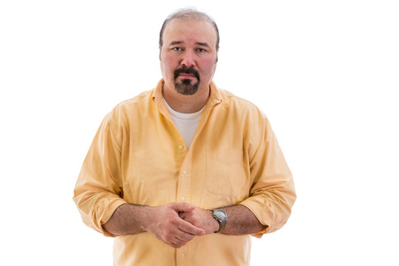 Compassionate sincere middle-aged man standing with clasped hands looking at the camera with an expression of empathy, isolated on white
