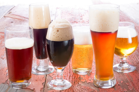 Variety of different beers, of different colors and alcoholic strengths in different shaped glasses suited to different personalities