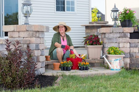 Happy stylish elderly Grandma planting in her garden sitting contentedly on the steps of her porch surrounded by plant seedlings in nursery trays transplanting into terracotta flowerpots