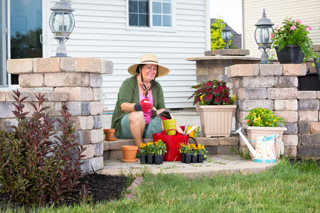 Happy elderly Grandma potting up plants sitting on the step of her patio with trays of nursery seedlings and a variety of terracotta flowerpots smiling contentedly at the camera in the spring sunshine