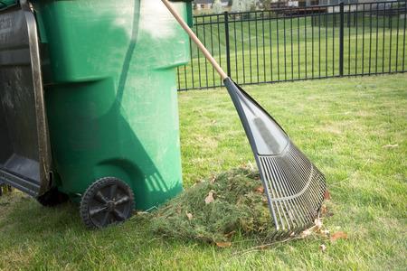 堆肥を施すことのプラスチック製ゴミ箱と一緒にきれいに刈り込まれた芝生の上の切り抜きや手あぶり熊手立ってのヒープと庭のメンテナンス中に春の草の切り抜きをかき集め