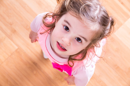 Photo for Pretty little girl with curly hair and beseeching eyes standing looking up into the camera as she asks for something that she wants, view looking down into her face with wood floor background - Royalty Free Image
