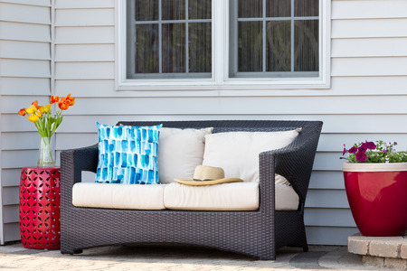 Comfortable outdoor living area on a brick patio with a deep seating settee and cushions flanked by red ceramic pedestal table and flowerpot with spring flowers and a straw sunhat