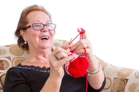 Happy elderly lady enjoying a joke laughing as she concentrates on her colorful festive red knitting while relaxing in a comfortable armchair, isolated on white