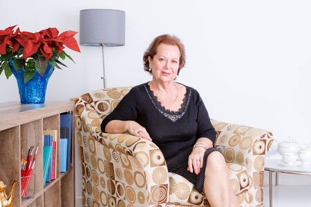 Photo pour Gracious elegant senior woman relaxing at home in a comfortable armchair sitting smiling at the camera, festive red poinsettia flowers in a vase - image libre de droit