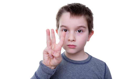 Photo pour Close up of serious little boy gesturing with three fingers as if to count or display a symbol - image libre de droit