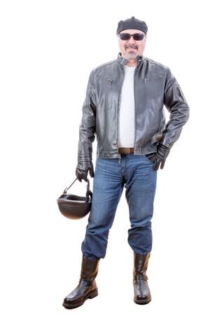 Tough handsome middle aged bearded man in motorcyclist outfit with boots holding helmet as he stands over white background smiling