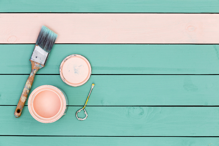 Photo pour Top down view of paintbrush, bolt, paintcan and green boards for paneling or flooring starting to be painted pink - image libre de droit