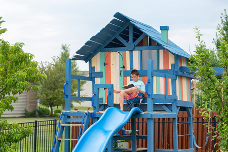Happy little boy in shorts seated comfortably in chair on freshly painted outdoor personal playground with slide and ladders
