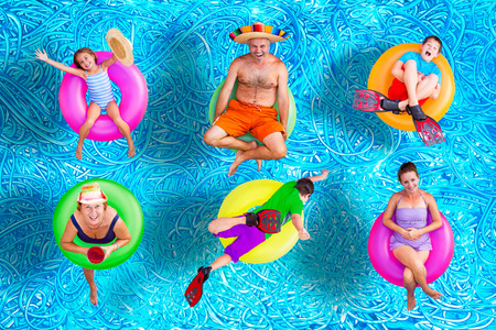 Foto de Family fun in the swimming pool in summer with a father, mother, grandmother, boys and a girl floating on colorful inner tubes in their swimsuits in various positions, conceptual image - Imagen libre de derechos