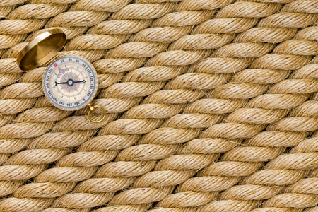 Small magnetic compass on diagonal strands of a new natural fiber rope conceptual of nautical navigation and shipping or of terrestrial exploration and mountain climbing in a full frame background