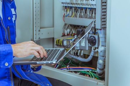 Photo pour Male engineers are checking the electrical system by program in laptop. - image libre de droit