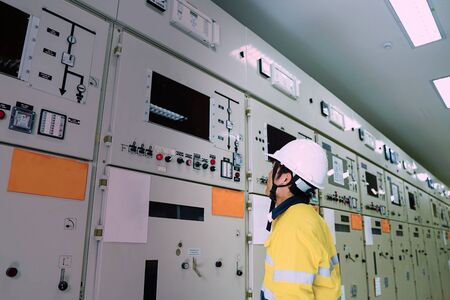 Photo for Male engineer wearing a yellow uniform and wearing a white safety hat, inspecting electrical systems in a large power plant. - Royalty Free Image