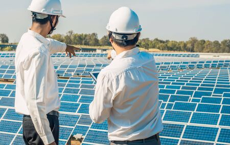 Photo for The solar farm(solar panel) with two engineers are talk about the production capacity, Alternative energy to conserve the world's energy, Photovoltaic module idea for clean energy production. - Royalty Free Image