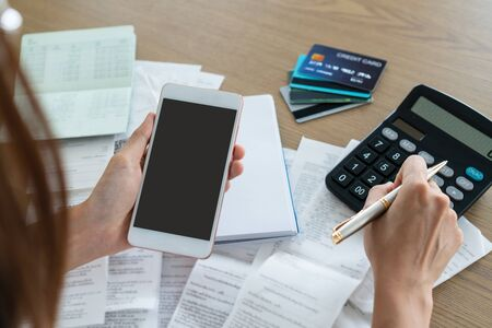 Photo pour Woman holding mobile phone and using calculator , account and saving concept. - image libre de droit