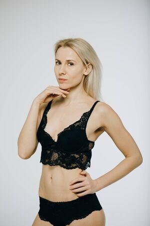 Photo pour Sensual blonde beautiful woman posing in elegant black lingerie, looking at camera. White background. - image libre de droit