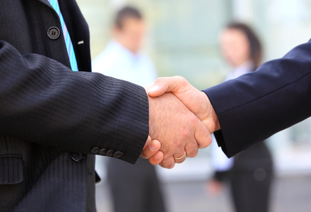 Closeup of business people shaking hands over a dealの写真素材