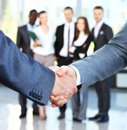 Photo pour Closeup of a business handshake. Business people shaking hands, finishing up a meeting - image libre de droit