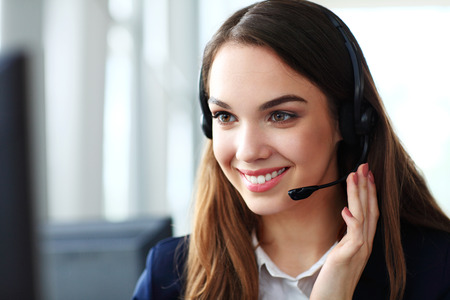 Foto de Female customer support operator with headset and smiling - Imagen libre de derechos