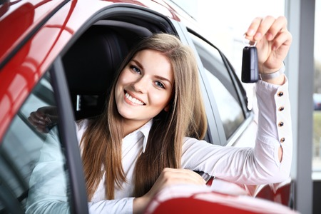 Woman Driver Holding Car Keys siting in Her New Car