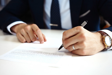 Businessman signing a document.