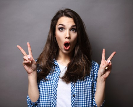 Photo pour Portrait of a happy woman showing victory with fingers over gray background - image libre de droit