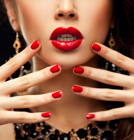 Photo pour Red Sexy Lips and Nails closeup. Open Mouth. Manicure and Makeup. Make up concept. Half of Beauty model girl's face isolated on black background - image libre de droit