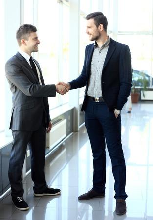 Foto de businesss and office concept - two businessmen shaking hands in office - Imagen libre de derechos